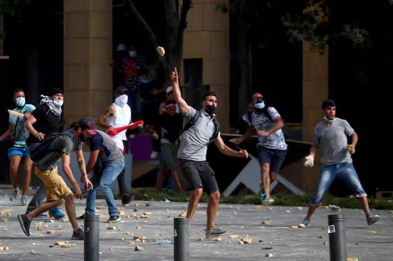 Demonstrators hurl stones during a protest near the parliament building following Tuesday's blast, in Beirut, Lebanon August 8, 2020. REUTERS/Hannah McKay