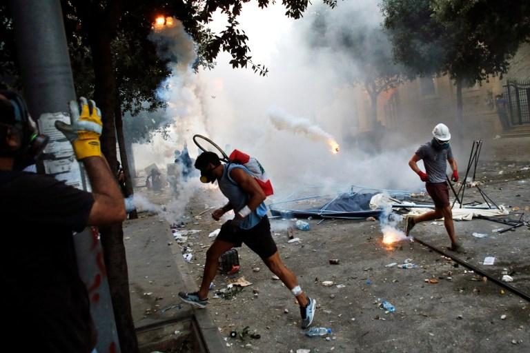 Des manifestants ont fui une cartouche de gaz lacrymogène lors d'affrontements avec la police dans le cadre d'une manifestation contre les élites politiques et le gouvernement après l'explosion meurtrière de cette semaine au port de Beyrouth qui a dévasté de grandes parties de la capitale à Beyrouth, au Liban, le samedi 8 août 2020 (Photo AP / Thibault Camus)