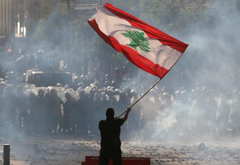 Un manifestant agite le drapeau libanais devant la police anti-émeute lors d'une manifestation à Beyrouth, au Liban, le 8 août 2020. REUTERS / Goran Tomasevic TPX IMAGES DU JOUR