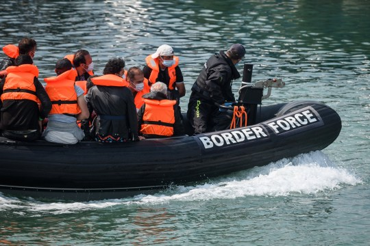 DOVER, ENGLAND - AUGUST 11: Migrants arrive in port aboard a Border Force vessel after being intercepted while crossing the English Channel from France in small boats on August 11, 2020 in Dover, England.