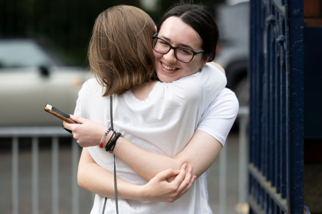 students hugging after receiving their a levels