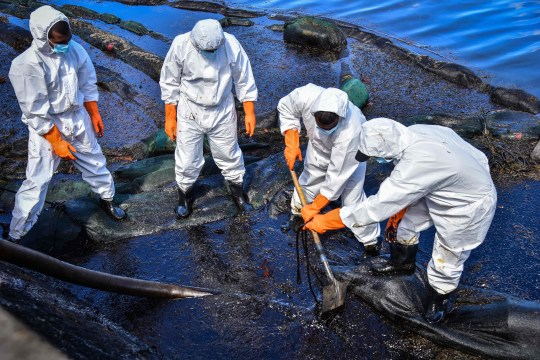 TOPSHOT - Volunteers collect leaked oil from the MV Wakashio bulk carrier that had run aground at the beach in Bois des Amourettes, Mauritius, on August 13, 2020. - Mauritius avoided a second catastrophic oil spill on August 12, 2020, after salvage crews pumped the remaining fuel from the tanks of a cargo ship that ran aground off its coast, imperilling world-famous wildlife sanctuaries. (Photo by Beekash Roopun / L'Express Maurice / AFP) (Photo by BEEKASH ROOPUN/L'Express Maurice/AFP via Getty Images)