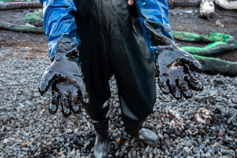 Un ouvrier tend ses bras recouverts d'huile épaisse provenant de la collecte d'algues et de paille mélangées à de l'huile qui fuit du MV Wakashio.