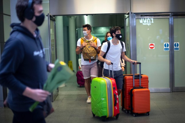 Travellers wearing face masks arrive from Paris to St Pancras Station