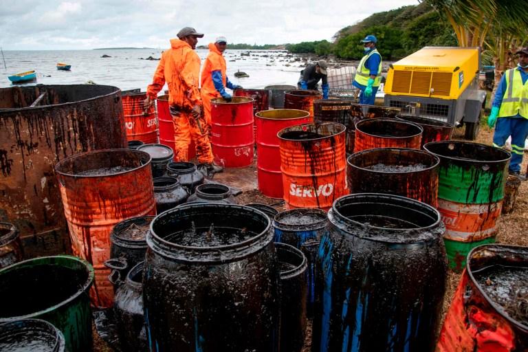 Les travailleurs récupèrent les fuites d'huile à la plage de Rivière des Créoles.