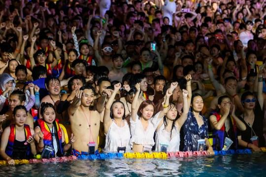 Cette photo prise le 15 août 2020 montre des gens qui regardent un spectacle en se rafraîchissant dans une piscine à Wuhan, dans la province centrale du Hubei en Chine.  (Photo par STR / AFP) / China OUT (Photo par STR / AFP via Getty Images)