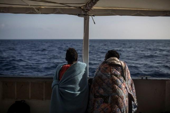 TOPSHOT - Des migrants regardent la mer depuis le pont du bateau de l'ONG Proactiva Open Arms le 2 juillet 2018. - Le bateau de l'ONG Proactiva Open Arms, qui avait secouru 59 migrants alors qu'ils tentaient de traverser la Méditerranée depuis la Libye, devrait accoster à Barcelone le 4 juillet 2018 après que l'Italie et Malte ont refusé l'accès.  (Photo par Olmo Calvo / AFP) (Photo par OLMO CALVO / AFP via Getty Images)