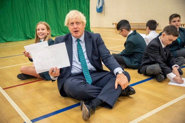 Britain's Prime Minister Boris Johnson gestures, during a visit to Castle Rock school on the pupils' first day back, in Coalville, East Midlands, England, Wednesday, Aug, 26, 2020. Following mounting pressure to change tack, the British government decided late Tuesday to ditch its advice that high school students in England don???t need to wear face masks while at school. In another in a series of abrupt changes in coronavirus-related policy, the government said children in secondary schools ??? those above 11 years of age ??? in areas under local lockdown rules, such as Greater Manchester, will have to don face masks when moving around corridors and communal areas. (Jack Hill/Pool Photo via AP)