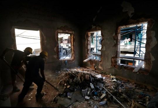 Les travailleurs enlèvent les débris de l'intérieur d'une maison qui a été détruite par l'explosion.
