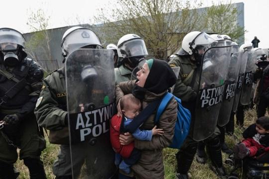Une femme tient un enfant alors que d'autres affrontent la police anti-émeute grecque à l'extérieur d'un camp de réfugiés à Diavata, une banlieue ouest de Thessalonique, où des migrants se rassemblent le 5 avril 2019. - Des centaines de migrants et de réfugiés se sont rassemblés à la suite d'appels anonymes sur les réseaux sociaux pour marcher jusqu'à ce que le Frontières nord de la Grèce pour passer à l'Europe.  (Photo par Sakis MITROLIDIS / AFP) SAKIS MITROLIDIS / AFP / Getty Images