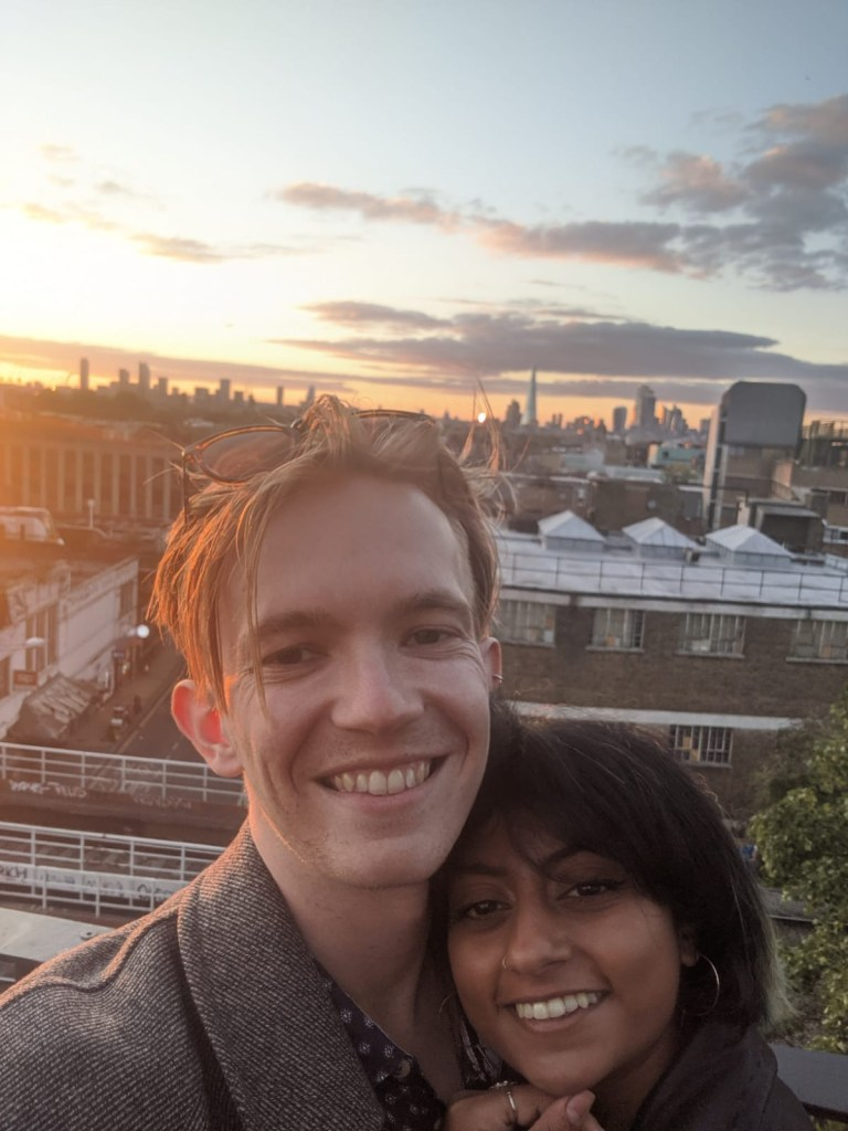 Tom and Immy in front of a backdrop of London