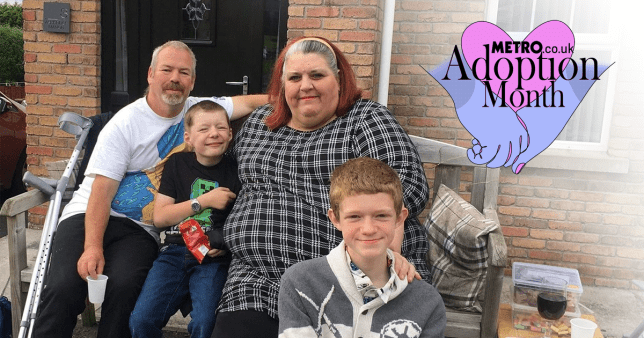 Alison and her husband and two boys sitting on a bench outside their house.