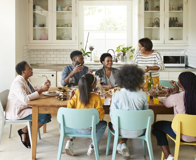 A large family sit around a dining table having fun