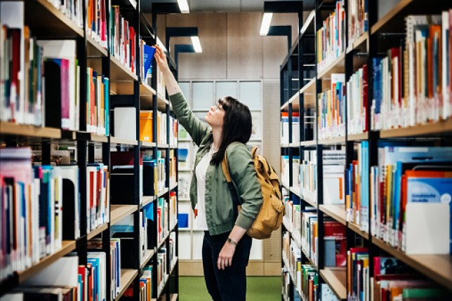 Student Selecting Book From Shelf In Library