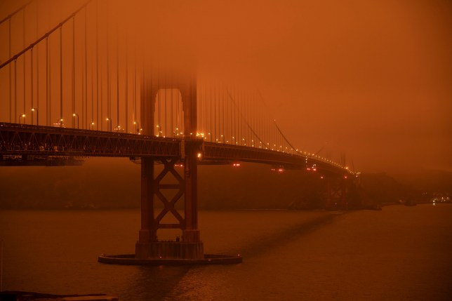 Cars drive along the Golden Gate Bridge under an orange smoke filled sky in San Francisco