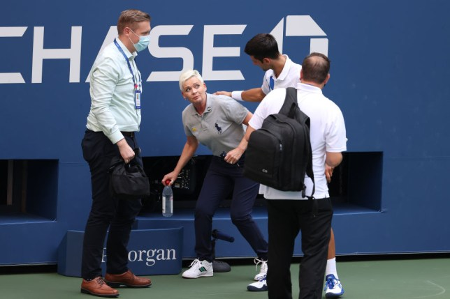 Novak Djokovic of Serbia tends to a lineswoman after inadvertently striking her with a ball hit in frustration during his Men's Singles fourth round match against Pablo Carreno Busta of Spain on Day Seven of the 2020 US Open at the USTA Billie Jean King National Tennis Center on September 6, 2020 in the Queens borough of New York City. Djokovic was defaulted from the match.