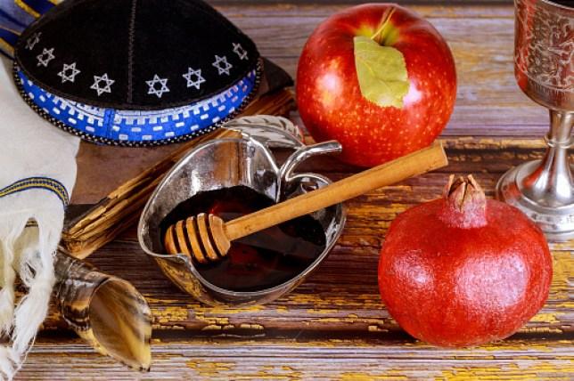 Shofar and tallit with glass honey jar and fresh ripe apples. Jewesh new year symbols.