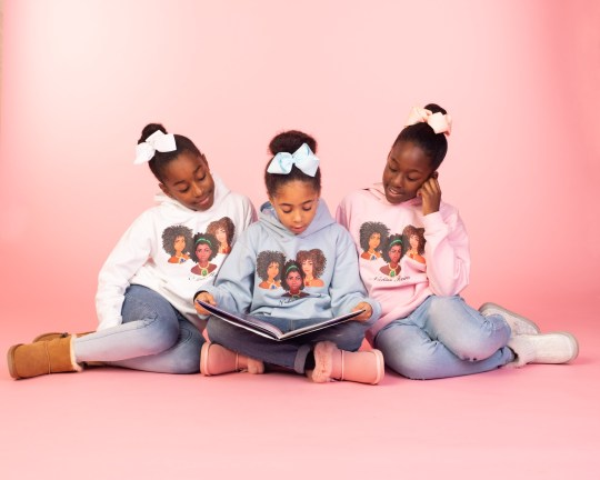 Three black girls sitting on the floor together and reading a book against a pink background.