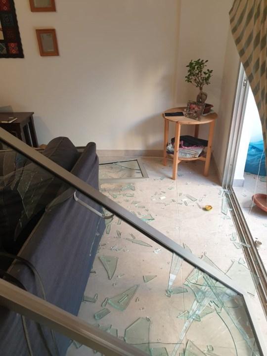 Salon frappé par l'explosion de Nidal Ali, avec une fenêtre tombée et du verre brisé