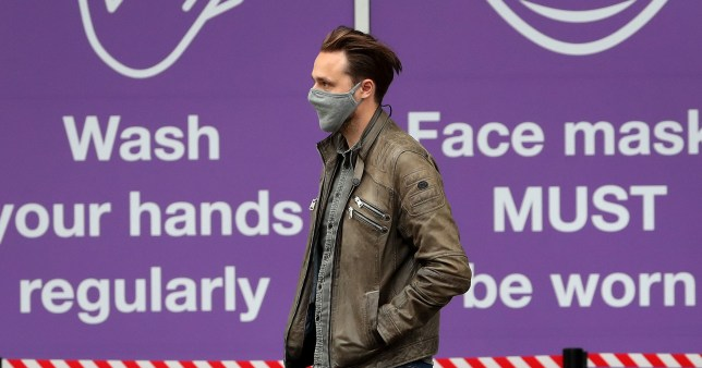 A man wearing a face mask walks past signs warning about coronavirus in Glasgow.