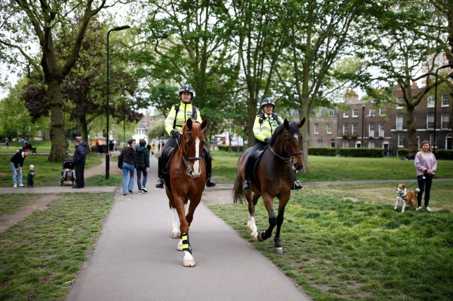 Police on horses talk to people at Victoria Park, following the outbreak of coronavirus disease in May