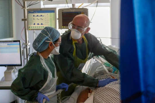 Doctors treat a patient suffering from coronavirus on an Intensive Care ward