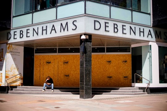 A man sits in front of a closed Debenhams department store on Oxford Street in central London's main high street retail shopping area on May 29, 2020 ahead of some shops reopening from their coronavirus shutdown from next week. - The UK Prime Minister announced on May 28 that some English schools and shops would reopen from next week people would a little more freedom to meet others in public as he tried to plot Britain's path through a health disaster that has officially claimed 37,837 lives -- second only to the United States -- and devastated the economy. (Photo by Tolga AKMEN / AFP) (Photo by TOLGA AKMEN/AFP via Getty Images)