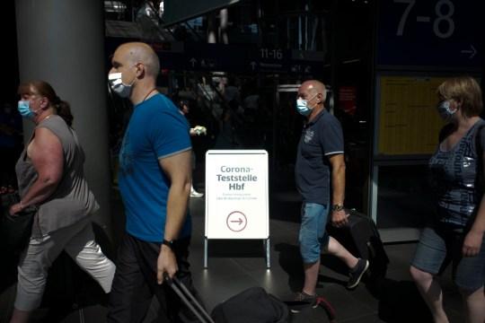 Les personnes portant des masques faciaux passent une affiche indiquant la direction d'une nouvelle station de test de coronavirus à la gare principale de Berlin, Allemagne