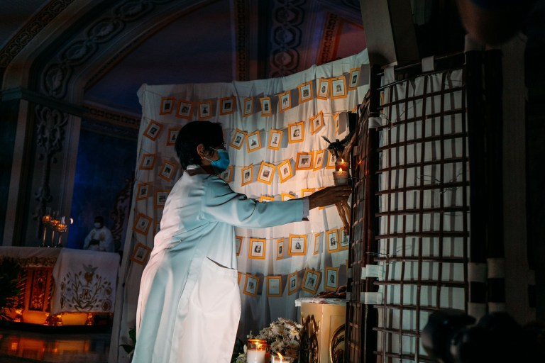 A doctor lights a candle during a mass for COVID-19 frontliners at the San Felipe Neri Parish in Mandaluyong City, on National Heroes Day, in Manila, Philippines