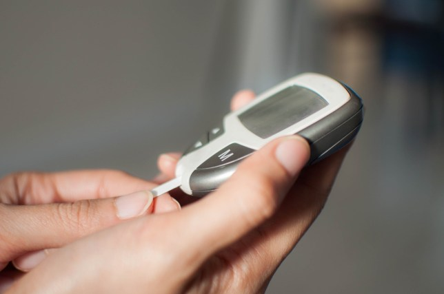 A close-up of a young woman is using a blood sugar device