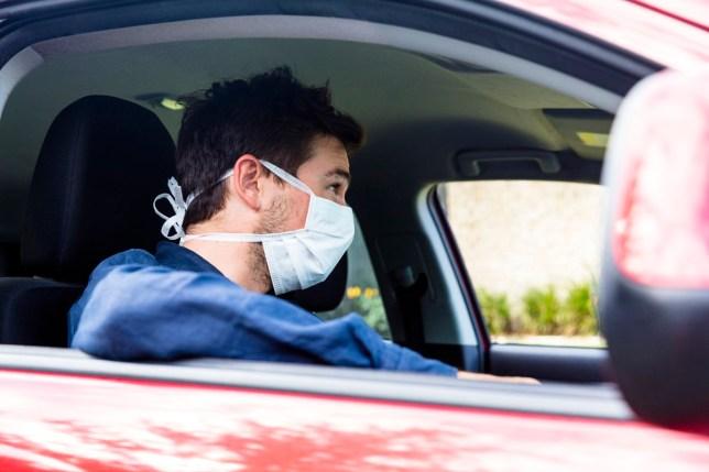 Jeune conducteur à l'intérieur de la voiture avec un masque protecteur