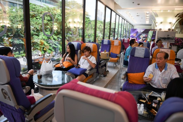 Customers eat at Thai Airways pop-up airplane-themed restaurant at the airlines headquarters with onboard meals prepared by their chefs, while their fleet is still grounded at the airport