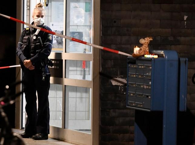Une policière se tient devant l'entrée d'une maison, jeudi 3 septembre 2020, à Solingen, en Allemagne.  La police affirme que cinq enfants ont été retrouvés morts dans un appartement d'une ville de l'ouest de l'Allemagne et que leur mère est soupçonnée de les avoir tués.  Les corps de trois filles et de deux garçons ont été retrouvés jeudi à Solingen, près de Cologne et de Düsseldorf.  La police a déclaré que la mère de 27 ans des enfants avait sauté plus tard devant un train à Düsseldorf et avait été emmenée à l'hôpital avec des blessures.  (Roberto Pfeil / dpa via AP)