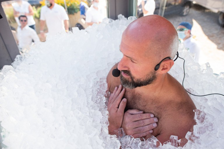 Josef Koeberl stands in a glass box filled with ice breaking the world record for the longest duration full body contact with ice on September 05, 2020 in Melk, Austria.