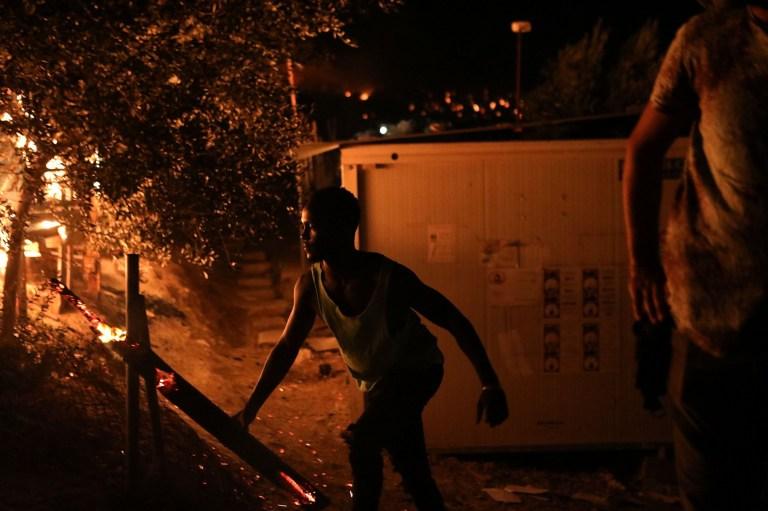 Un migrant déplace une bûche en feu alors qu'un feu brûle au camp de Moria sur l'île de Lesbos, en Grèce, le 9 septembre 2020.