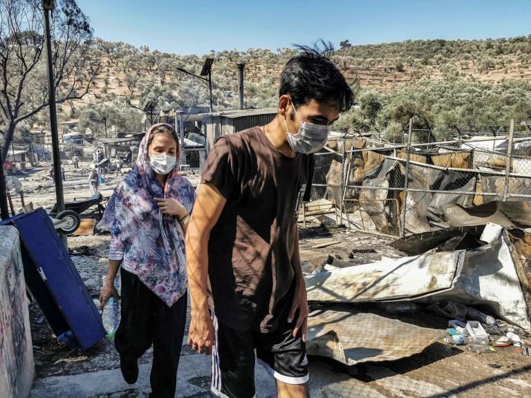 Des migrants marchent à l'intérieur du camp de Moria incendié sur l'île grecque de Lesbos le 9 septembre 2020, après un incendie majeur.