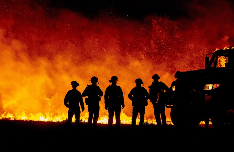 Butte County firefighters watch as flames quickly spread across a road at the Bear fire in Oroville, California on September 9, 2020.