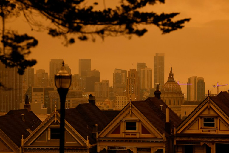 Une vue des Painted Ladies, la rangée emblématique de maisons victoriennes historiques avec un fond de centre-ville, sous un ciel couvert orange dans l'après-midi à San Francisco, Californie, États-Unis, 09 septembre 2020.