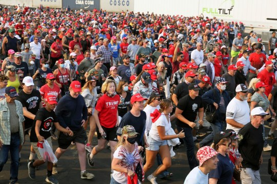 Supporters for President Donald Trump run to the stage area of a political rally at the Minden-Tahoe Airport prior to the start of a rally for Trump in Minden, Nevada, Saturday, Sept. 12, 2020.