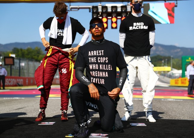 Lewis Hamilton wears a t-shirt displaying the message 'arrest the cops who killed Breonna Taylor' as he takes a knee on the grid in support of ending racism before the F1 Grand Prix of Tuscany at Mugello Circuit.