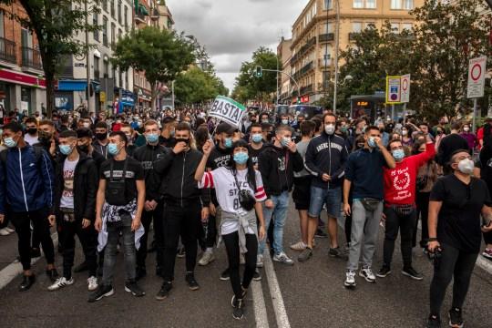 Des manifestants portant des masques de protection crient des slogans alors que l'on tient une pancarte indiquant `` Assez '' lors d'une manifestation, dans le quartier de Vallecas, contre les mesures imposées par le gouvernement régional de Madrid sur les zones avec le plus de cas de Covid-19 le 20 septembre 2020 à Madrid, Espagne.
