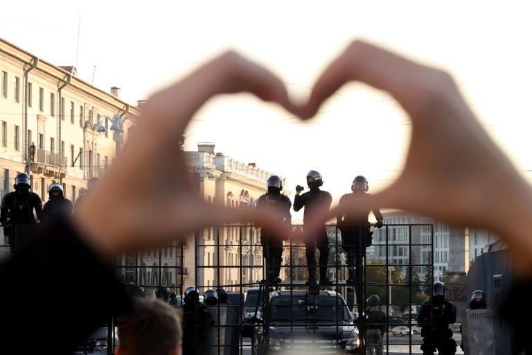 Une femme fait des gestes en forme de cœur alors qu'elle se tient devant des agents des forces de l'ordre bloquant la route lors d'une manifestation appelée par le mouvement d'opposition pour la fin du régime du chef autoritaire à Minsk le 20 septembre 2020.
