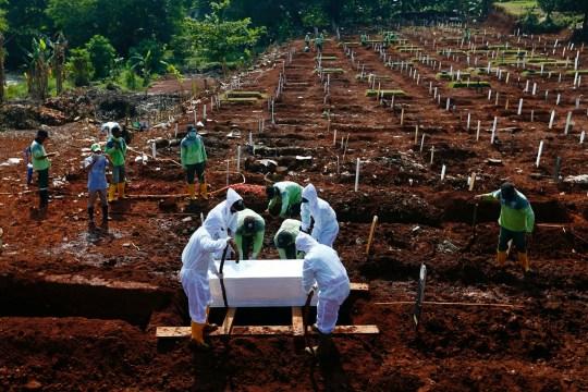 Des travailleurs portant des combinaisons de protection enterrent un cercueil dans la zone de sépulture musulmane fournie par le gouvernement pour les victimes de la maladie à coronavirus (COVID-19) au complexe du cimetière de Pondok Ranggon à Jakarta, Indonésie, le 16 septembre 2020. REUTERS / Ajeng Dinar Ulfiana