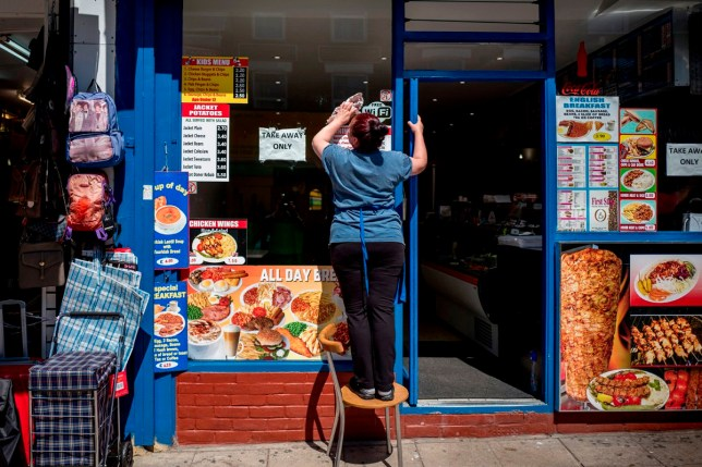 A shop worker cleans the the windows of a restaurant, now serving take-away food only due to the COVID-19 pandemic, in Walthamstow, east London on June 22, 2020. - Britain's current social distancing guidelines set the distance between each person at two metres to avoid the risk of contamination to coronavirus. There is pressure on the government to reduce this distance in order to give a boost to bars, restaurants and hotels, which are scheduled to reopen next month. (Photo by Tolga AKMEN / AFP) (Photo by TOLGA AKMEN/AFP via Getty Images)