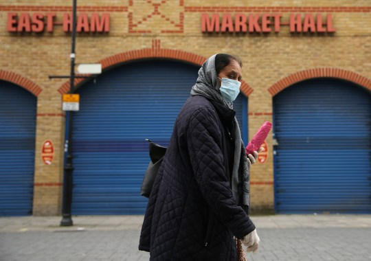 A woman wearing protective personal equipment walks past a closed-down East Ham Market Hall, east London, as the UK continues in lockdown to help curb the spread of the coronavirus. Picture date: Tuesday April 28, 2020.
