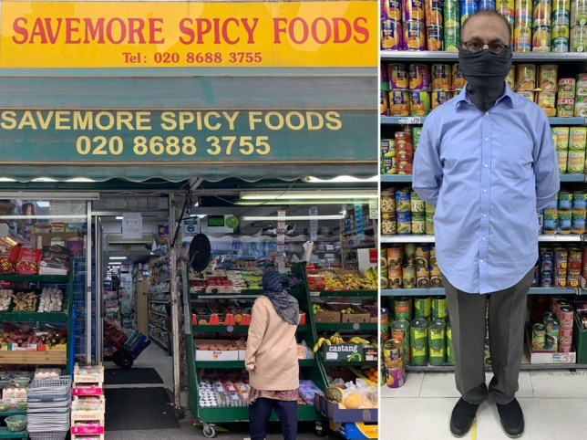 A shop-owner wearing a black face mask stands in front of shelves stacked with food products.