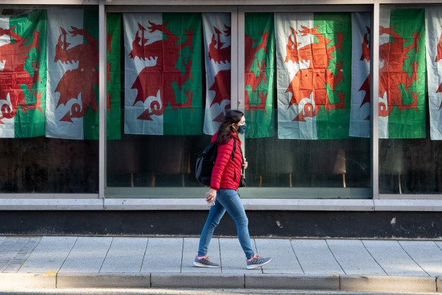 A woman wearing a face covering walks past a nightclub with Wales flags hanging in their window, as new coronavirus restrictions come into effect from Thursday.