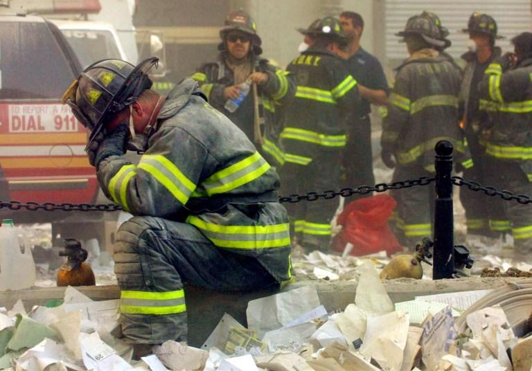 Photographie d'un pompier à genoux avec sa tête dans ses mains