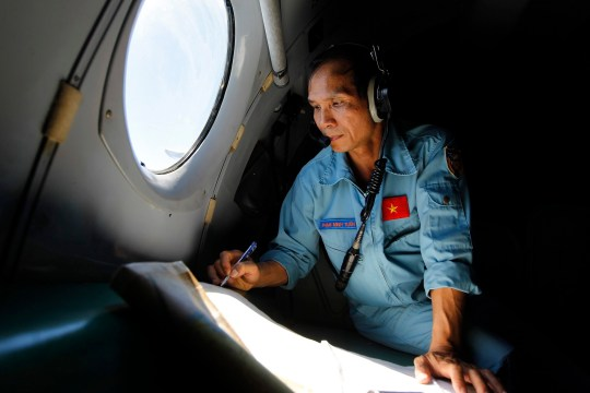 A Vietnamese military official works inside a flying Soviet-made AN-26 of the Vietnam Air Force during search and rescue operations for a missing Malaysian Airlines flight, off Vietnam's sea on 13 March 2014. Vietnam fully resumed its search for the Malaysia Airlines plane that went missing, after communicating with Malaysian authorities over media reports, subsequently denied, regarding the plane's last known location. Malaysia Airlines flight MH370 with 239 people on board went missing early 08 March 2014 while on its way from Kuala Lumpur, Malaysia, to Beijing, China. EPA/LUONG THAI LINH epa04122677