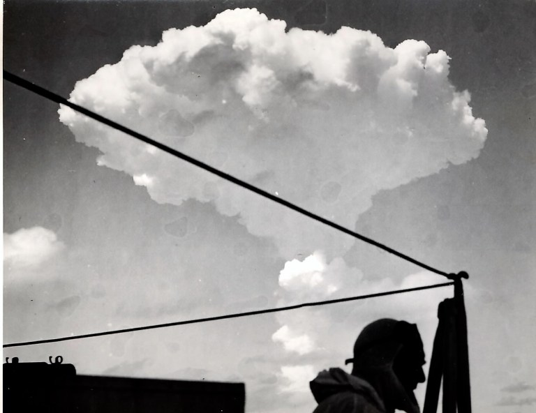 A black and white image of Bryan Pitt in front of an H bomb cloud